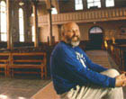 Don Cyr sits inside Notre Dame du Mont-Carmel Church in Lille, 1995. He has made a great effort to restoring this unique church to its original beauty.  Photographer, Paula Lerner,   2003.